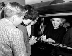 Marilyn Monroe signing autographs for children upon arriving at then-Idlewild Airport, 1956.