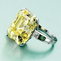FANCY INTENSE YELLOW DIAMOND RING, CIRCA 1930 The emerald-cut fancy intense yellow diamond weighing 8.73 carats, flanked by 4 baguette and bullet-cut diamonds and 2 square-cut emeralds, mounted in platinum
