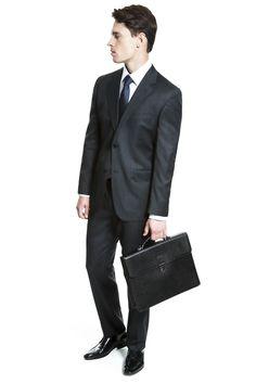 Camisa falso liso azul, gravata marinho com poá, costume chumbo falso liso, pasta preta de couro texturizado e sapato clássico de amarrar em couro box.