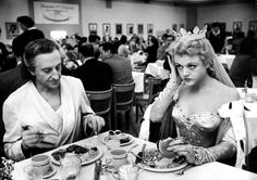 """Angela Lansbury, in costume for her role in """"The Court Jester"""", eats lunch with Basil Rathbone in the Paramount Studio commissary, December 1954."""