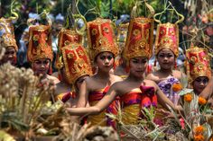 Women dance through the streets in a festival in Ubud, Bali