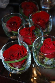 Green and red centerpieces simply using the heads of roses coiled around with the stem around the rose.  A simple idea to consider.