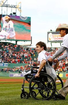 BOSTON, MA - MAY 28: Boston Marathon bombing victim, Jeff Bauman, is wheeled out to the pitchers mound before throwing out the ceremonial first pitch by Carlos Arredondo, the man who came to his aid immediately following the explosions, prior to the interleague game between the Boston Red Sox and the Philadelphia Phillies on May 28, 2013 at Fenway Park in Boston, Massachusetts. (Photo by Jared Wickerham/Getty Images)