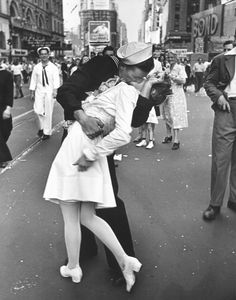 A jubilant Amer. sailor clutching a pretty white-uniformed nurse in a back-bending, passionate kiss as he vents his joy while thousands jam the Times Squar...