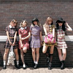 Japanese girls in plaid pleaded skirts and crop tops. Street fashion