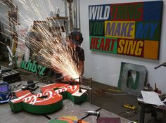 Artist David Buckingham cuts and welds recycled metal pieces to form sculptures of famous quotations, song lyrics, and pop culture symbols and objects