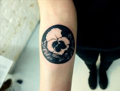 Black pansy in a circle black & white tattoo by Stan Wilczynski at Faux Pas Tattoo Gallery, Moscow