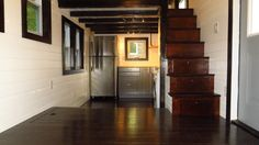 This is an 8'x30′ double-loft tiny cottage on wheels with floor storage built by Brevard Tiny House Company. It's called the 36° North. When you go inside you'll find a gorg…