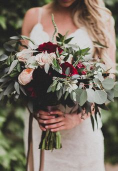 Early spring wedding bouquet inspiration. We love the deep reds. and green foliage.
