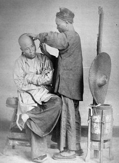 Close shave: A street barber carefully cuts a client's hair in this image from China Magazine taken in the late 1860s. The photographs sold today for £12,000 - six times their guide price