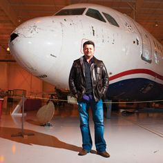 Ben Bostic, passenger of flight 1549 which crashed into the Hudson River after hitting a flock of geese poses with the fuselage of the plane at the Carolinas Aviation Museum.