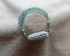 This is a handmade crochet pouch to carry your fit bit flex in. The beads are glass and about 8mm in size. Bracelet is 7 1/2 inches long. The fit bit slips in like putting on a slipper. Will be a little snug but you want security. The only drawback if you like to check your steps all the time the lights are not visible. Your fit bit is secure and fashionable as well. THIS IS DESIGNED TO FIT THE FITBIT FLEX, I CAN ALSO MAKE ONE TO FIT THE FITBIT ONE. PLEASE PERSONAL MESSAGE ME