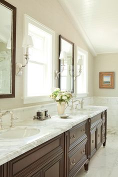 The vanity stands below sun filled windows which are flanked by matching vanity mirrors