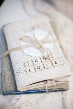 Rustic table decor idea for a wedding: Add old novels wrapped in burlap or hessian and dressed up with scrabble letters
