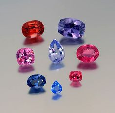 SPINEL spectacle: Clockwise from top left, 8.07-ct orangey red Burma oval, 12.37-ct lavender Burma cushion, 7.11-ct pinkish red Tanzania oval, 1.8-ct flame red Burma cushion, 1.26-ct cobalt blue Vietnam pear shape, 3.73-ct cobalt blue Burma oval, 6.14-ct purply pink Tajikistan cushion. Center, 5.90-ct violet blue Vietnam pear shape.