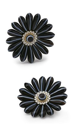 Attributed to Carlo Giuliano - A pair of antique gold, black agate and enamel brooches, English, circa 1890. The black agate petals with vertical white bands, centred by banded agate pistels within elliptical opaque white enamel stamen, mounted in yellow gold.