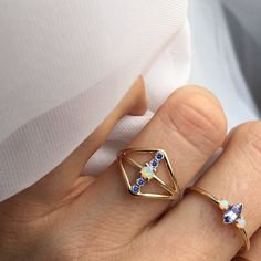 -solid 14kt gold -3mm Australian opal -1.4mm faceted tanzanites Bold, yet still delicate ring made up of faceted tanzanites and a central Australian opal. *100% hand-crafted in the USA *FREE shipping