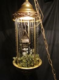 My grandmother use to have one of these...   Rain Lamps.  Oil would drip down the plastic strings.