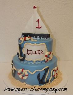 two tier fondant birthday cake with sailboat cake topper, anchors and life perservers.