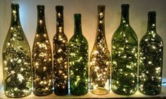 Elegant lights - the lights accent the lovely shape of the bottles. Against the white background, this is a lovely arrangement. #WineBottleLamps #CraftLights #ChristmasLights