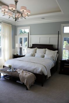 This bedroom looks very inviting with the gray,white paneled walls and dark furniture