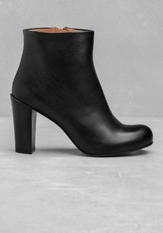 High heeled leather ankle boots, featuring a zip with a leather handle for a slim-fitting closure.