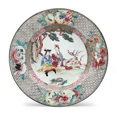"""A """"CANTON ENAMEL"""" RUBY BACK EUROPEAN SUBJECT PLATE  YONGZHENG/EARLY QIANLONG PERIOD  A European couple sits under trees, a stack of books beside them, the rim with finely painted clusters of fruit, flowers and insects against a patterned ground, the back rim a mottled ruby, stylized blue dragon in the center 8 3/8 inches (21.2 cm) diameter"""
