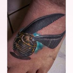 Den Hor tattooed a realistic Golden Snitch on the foot of his client.