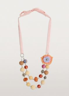 A necklace with big appeal! A crocheted rosette is offset by bold beads in fabric and white metal. Playful and fun.