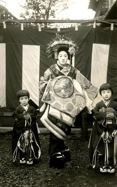Tayuu and Kamuro in front of a Kohaku-maku, 1920s.  This postcard shows a Tayuu (Japanese Courtesan) and two Kamuro (Child Attendants) standing in front of a Kōhaku-maku (red and white curtain). A Kōhaku-maku is a type of decorative fabric panel used on various occasions in Japan, such as outdoor tea ceremonies. S)