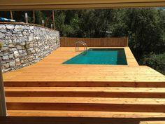 Piscina Laghetto Dolcevita Gold con 2 skimmer, telo di rivestimento di color verde, scala inox e pavimentazione deck in legno. Piscina realizzata da Sanipool Srl di Carasco (GE).