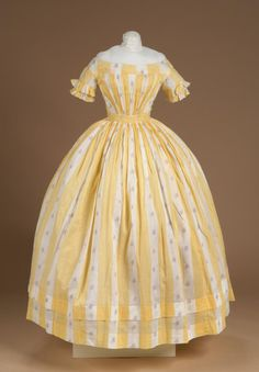 Circa 1850 dress of printed cotton with repeating design of solid yellow vertical stripe and white stripe with purple and red flowers. full skirt (bell shaped) gathered at waist, and has two hems. Via Litchfield Historical Society. 1850s Fashion, Victorian Fashion, Vintage Fashion, Victorian Era, Vintage Outfits, Vintage Dresses, Vintage Clothing, Old Dresses, Cotton Dresses
