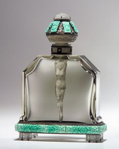 "HOFFMAN Czech perfume bottle ""Nude dauber"" in grey crystal, the stopper wand designed as a nude wrapped in a floral scarf. Elaborate mounting in silver metal, marcasites, and crystal jewels, stopper crowned by crystal cameo Medusa, 1920s. Intaglio HOFFMAN mark on stopper and bottle. Metal stamped AUSTRIA. Ht. 8 in."
