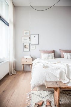 Wooden floor,  light grey wall, white curtain and bedsheets. Grey pink  cushions and little patterens. Wooden furnitures. Almost all white pictures with metal frames.