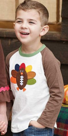 Boys Football Turkey T-Shirt for Thanksgiving. Everything you love about the fall season all in one fun boys Thanksgiving t-shirt! Dress him for festive fun int he comfy cotton slub knit turkey tee from Mud Pie. Available in sizes for infant and toddler boys.