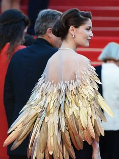 Laetitia Casta in Christian Dior Couture at the Zulu Premiere, 66th Cannes Film Festival. Cloak, cape with gold feathers. Interesting.