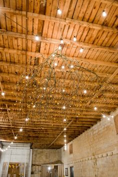 I love this branch chandelier idea with paper flowers in your colors. We could also DIY this one. The lighting is simple and affordable and looks great inside a barn.