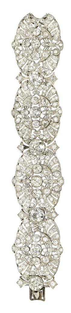 AN ART DECO DIAMOND BRACELET.   The articulated band of foliate motifs designed as four old-cut diamond pierced plaques, each centering upon three collet-set diamonds, to the diamond collet spacers, mounted in platinum, circa 1920, 18.2 cm long