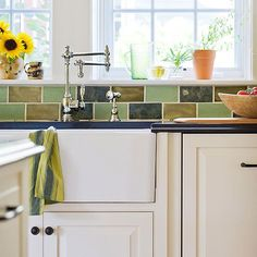 Subway tile in different shades of green wrap the kitchen, adding earthy tones and a burst of color to the white space.