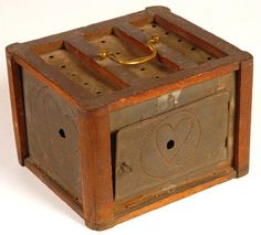 "Rare 19th C. Child's Foot Warmer  Walnut frame enclosing tinned iron sides. Untraditional brass bale handle instead of the customary bent wire, corners of the frame are shaped like a Massachusetts candlestand. The typical adult foot warmer was roughly 10"" or 11"" square; this version scaled for a child, is 6¾"" x 7¾"". It's probable that instead of a pan of glowing coals, for safety the warmth was provided by a heated brick wrapped in flannel. Ca. 1820-1830."