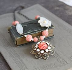 This is a lovely collage necklace, so elegant and such a glamorous use of antique and vintage jewelry parts. They key elements are of celluloid and Mother of Pearl. Each of the MOP elements along the chain itself are vintage/antique brooches. The long oval piece is finely carved and the floral piece is simply stunning. The centerpiece is a gorgeous salmon or coral colored celluloid and rhinestone brooch. The pin backs have been removed from the two mother of pearl brooches. The necklace...