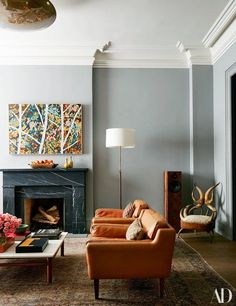 The living room, with a William Monk painting and a horn chair | archdigest.com
