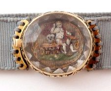 """Extraordinary Stuart Crystal clasp attached to a ribbon (not original) and used as a bracelet.    The amazing scene depicts a cherub (or putti) on a bench with an anvil. He rests his elbow on a skull. The word """"Hope"""" is underneath as well as the initials JC in gold wire thread. The background is tightly woven hair."""
