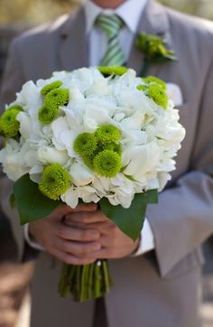 White bouquet of roses and hydrangea accented with bright green button mums  Think green hydrangea, yellow button mums, orange daisy mums, and red hypericum or red pepper berry.
