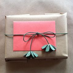 Jute rope with paper flowers knotted on ends or as pictured, leather cord with leather punched flowers to pretty up a simple package!