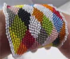 Finely beaded peyote stitch cuff bracelet, multi-coloured diamond pattern, featuring a collection of vintage  antique size 11  10 seed beads. 3 beaded ball and loop closures.    This piece is handbeaded not using a loom, but stitched bead to bead, one tiny seed bead at a time, forming a beaded fabric that drapes around the wrist.   6.5cm wide x 17.5cm long