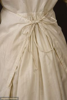 """Scallop-hem white dress, 1800-1815. Augusta Auctions: """"Tabby cotton, trimmed with drawnwork and darned net lace, apron front construction, square neckline edged with bobbin lace, buttoning on both sides at front armscye, short puff sleeves, slim skirt with extra fabric gathered at back, hem scalloped and trimmed with drawnwork."""""""