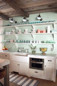 Open shelving - I never thought I would like this but I had an apartment with open shelving once and it was cool!  Add the green glass subway tile along with the rustic ceiling... oh yeah!  Don't forget the apron sink too.  Oooeeeeooooeeee me want!