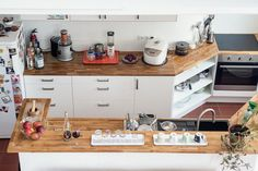 Schön eingerichtete Küche aus der Vogelperspektive: Arbeitsplatten aus Holz, weiße Fronten und alles, was man sonst noch braucht.  #Berlin #Küche #kitchen #interior