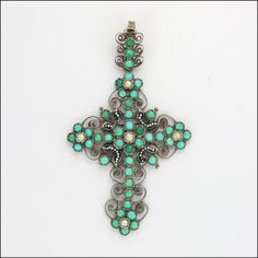 "This Austro-Hungarian cross pendant bears no marks (but tests to at least 800 quality) but has natural  turquoise and seed pearls + the enamelling typical of A-H jewellery. It may have originally been gold washed (remnants of which can be seen in the centerb back).  The cross measures 2 ¾"" (6.9cms) long, including the bail, and 1 5/8"" (4.1cms) across. It weighs 10.3 grams.  This cross is in fine antique condition with all the elements intact.   $535.00"